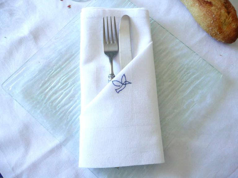 napkin ou pliage de serviette afin de pouvoir y insérer les couverts, avec une serviette brodée à la main