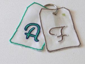 Initiales du prénom et du nom sur du tissu coton de récupération, montées avec un anneau métallique