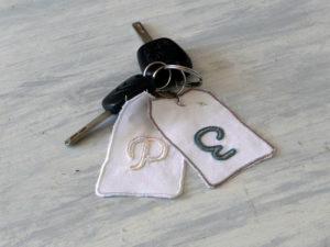 Initiales P et E brodées sur des étiquettes de tissu récupéré, elles sont montées en porte-clés