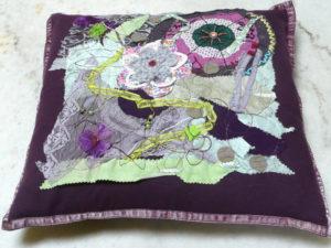 coussin décoré avec une création textile dans les tons de violet et une touche de vert anis